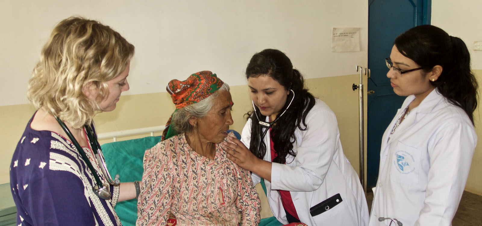 2 women in lab coats with a Nepalese female patient and a female volunteer