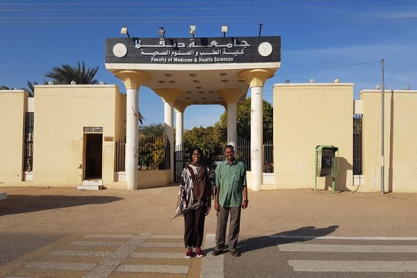 Woman and man standing in front of an entrance to a university