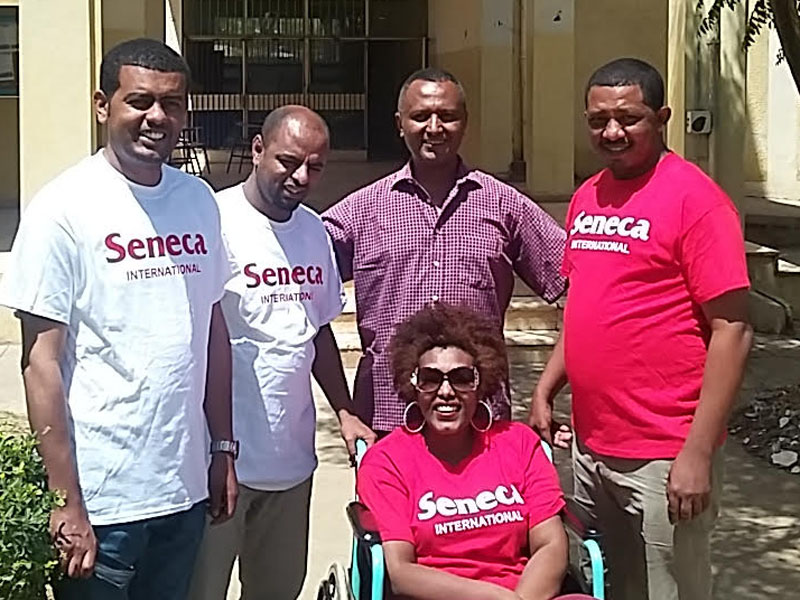 4 men standing side by side behind a woman sitting in a wheelchair